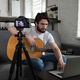 Man preparing for online guitar lesson - PhotoDune Item for Sale