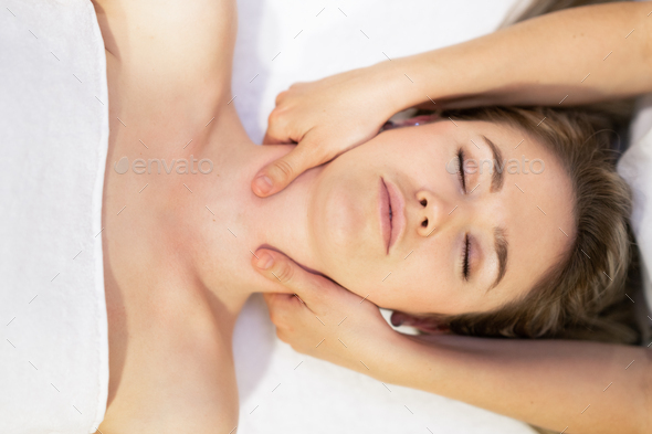 Young blond woman receiving a head massage in a spa center - Stock Photo - Images