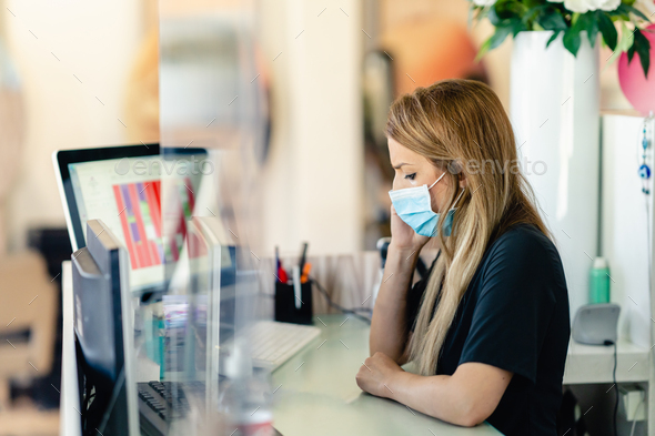 Female hairdresser answering the phone to give her clients an appointment, wearing a protective mask - Stock Photo - Images