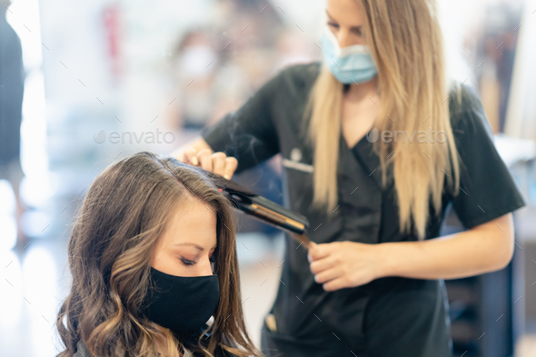Hairdresser, protected by a mask, combing her client's hair with a hair iron in a salon - Stock Photo - Images