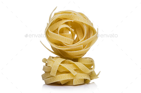 Coils of dried Italian pasta or noodles on white - Stock Photo - Images