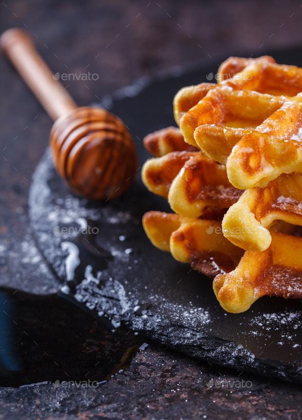 Belgian waffles with honey on a black background. - Stock Photo - Images