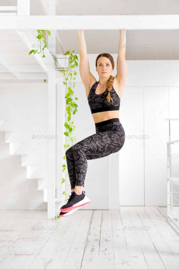 Woman working out doing a toes to bar exercise - Stock Photo - Images