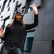 Woman Portrait Using Virtual Reality Glasses And Black Outfit In Futuristic City - PhotoDune Item for Sale