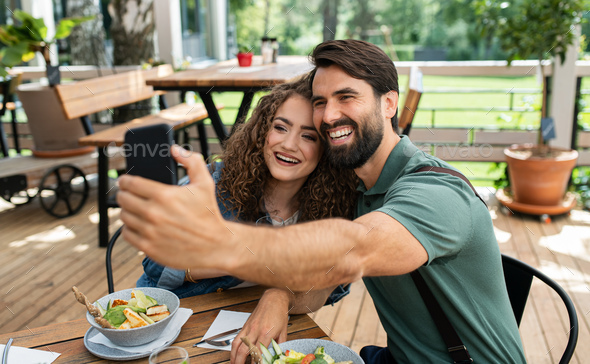 Happy couple sitting outdoors on terrace restaurant, taking selfie - Stock Photo - Images