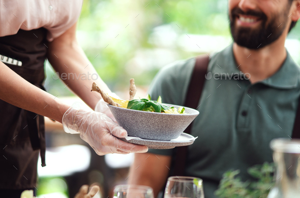 Unrecognizable waitres with gloves serving man outdoors on terrace restaurant - Stock Photo - Images