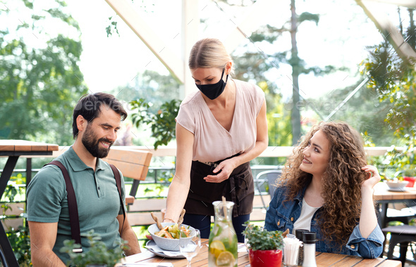 Waitress with face mask serving happy couple outdoors on terrace restaurant - Stock Photo - Images