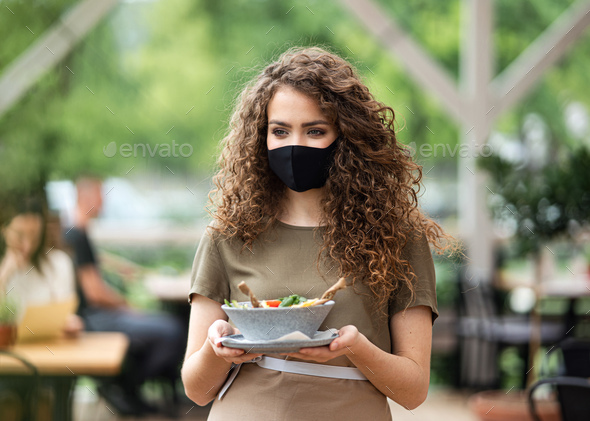 Waitress with face mask serving customers outdoors on terrace restaurant - Stock Photo - Images