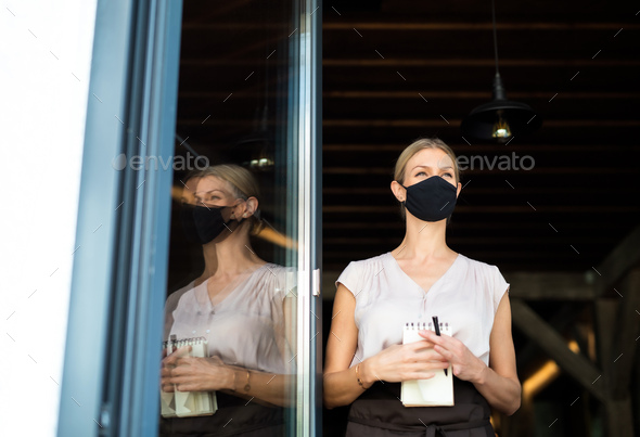 Portrait of waitress with face mask standing at the door in restaurant - Stock Photo - Images