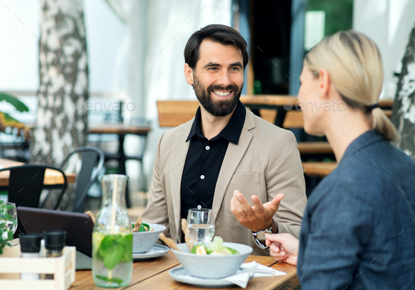 Happy couple sitting outdoors on terrace restaurant, talking - Stock Photo - Images