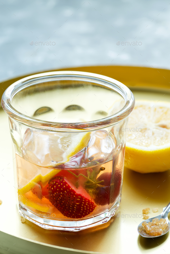 Homemade refreshing cold cocktail from natural berries and lemon fruits in a glass on a light grey - Stock Photo - Images