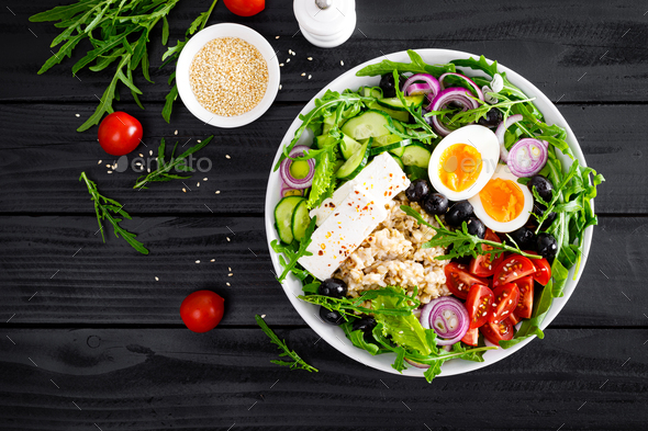 Greek style healthy breakfast bowl with oatmeal porridge and fresh vegetable salad - Stock Photo - Images