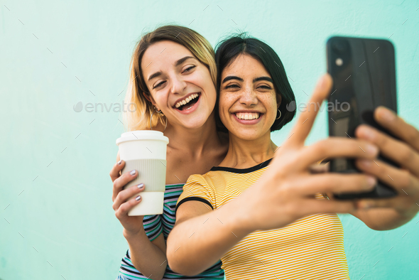 Lovely lesbian couple taking a selfie with phone. - Stock Photo - Images