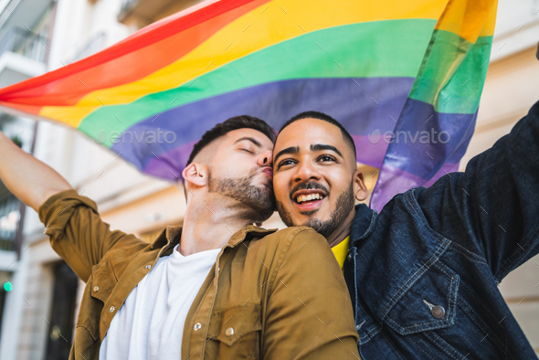 Gay couple embracing and showing their love with rainbow flag. - Stock Photo - Images