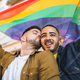 Gay couple embracing and showing their love with rainbow flag. - PhotoDune Item for Sale