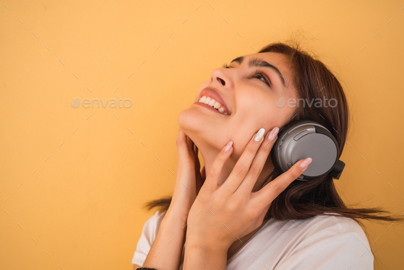 Young woman listening music with headphones. - Stock Photo - Images