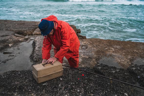 Fisherman with fishing equipment box. - Stock Photo - Images