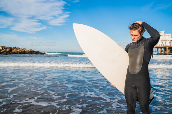 Surfer standing in the ocean with his surfboard. - Stock Photo - Images