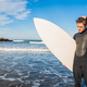 Surfer standing in the ocean with his surfboard. - PhotoDune Item for Sale
