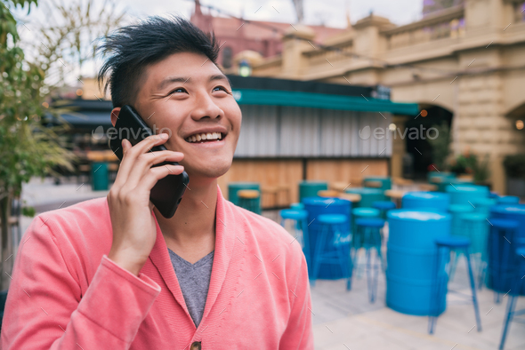 Asian man talking on the phone outdoors. - Stock Photo - Images