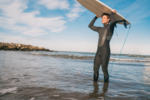 Young surfer holding up his surfboard. - Stock Photo - Images