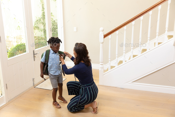 Mixed race woman saying goodbye to her young son - Stock Photo - Images