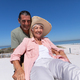 Senior Caucasian couple riding a bike at the beach - PhotoDune Item for Sale