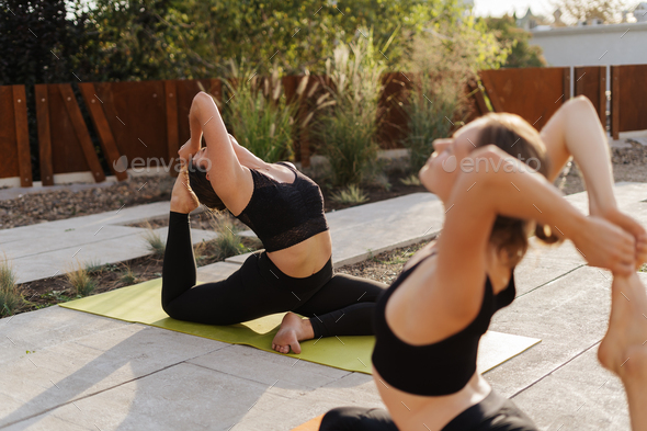 Two young girls practicing stretching and yoga workout exercise together - Stock Photo - Images