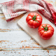 Top view of a white cutting board with a fresh juicy tomatoes on a wooden table - PhotoDune Item for Sale