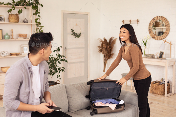 Joyful Travelers Couple Packing Suitcase For Vacation At Home - Stock Photo - Images