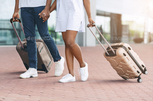 Unrecognizable afro couple walking with luggage outside of airport - Stock Photo - Images