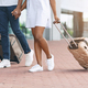 Unrecognizable afro couple walking with luggage outside of airport - PhotoDune Item for Sale