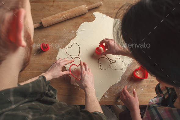 young lovely couple making cookies in heart shape - Stock Photo - Images