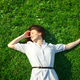 relaxed young brunette woman lie on grass green lawn at sunny day - PhotoDune Item for Sale