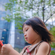 Asian child using cell phone in city - PhotoDune Item for Sale