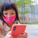 Asian child wearing mask and using cell phone in city - PhotoDune Item for Sale