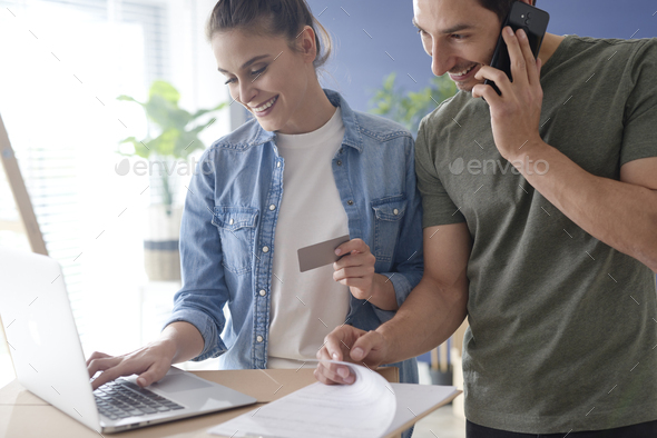 Happy couple doing shopping online for new house - Stock Photo - Images
