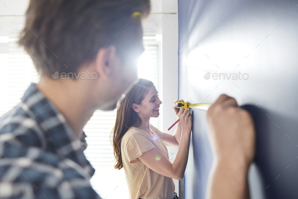 Cooperating couple using measure tape on the wall - Stock Photo - Images