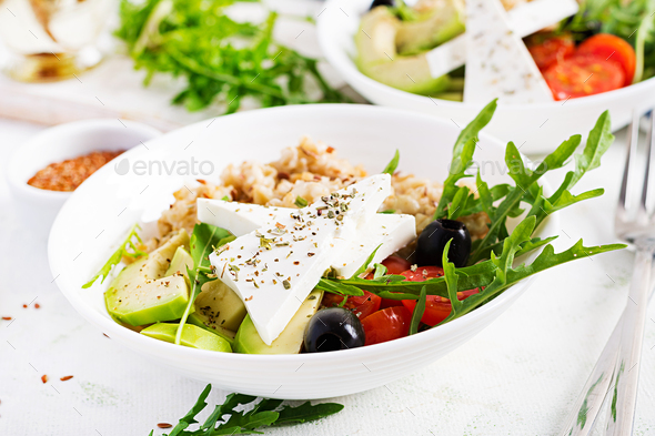 Breakfast oatmeal porridge with greek salad of tomatoes, avocado, black olives - Stock Photo - Images