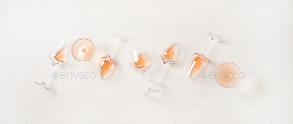 Flat-lay of rose wine in glasses over plain white background - Stock Photo - Images