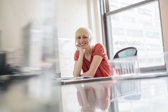Office life, A young woman sitting at an office desk, her chin resting on her hand - Stock Photo - Images