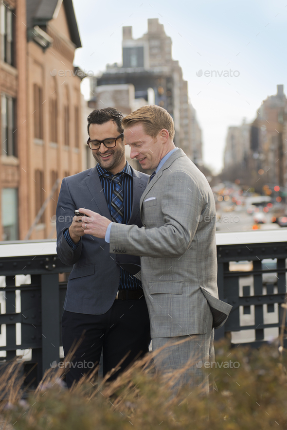 Two men in formal business clothes looking at a cell phone screen - Stock Photo - Images