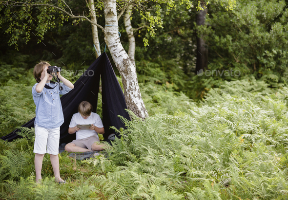 Two boys camping, one sitting under a black canvas shelter,  boy looking through binoculars, - Stock Photo - Images