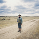 Man wearing cowboy hat and cowboy boots standing on a country lane in the Canadian Prairie. - PhotoDune Item for Sale