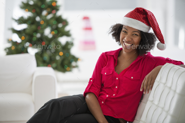 Woman in red and white Father Christmas hat by a Christmas tree - Stock Photo - Images