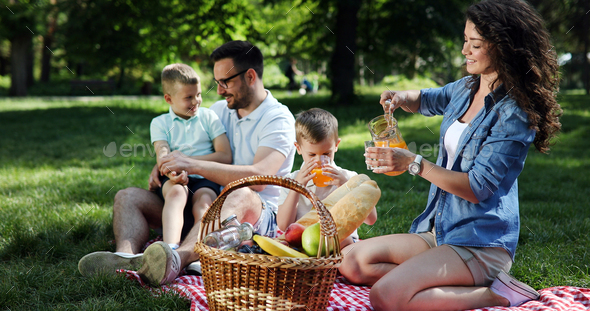 Cheerful happy family picnicking on a beautiful day - Stock Photo - Images
