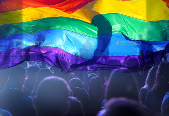 Colorful LGBT flag blows in the breez over crowd. - Stock Photo - Images