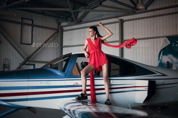 Fashion photo of model girl in a red dress standing on the wing of a propeller plane in the garage - Stock Photo - Images