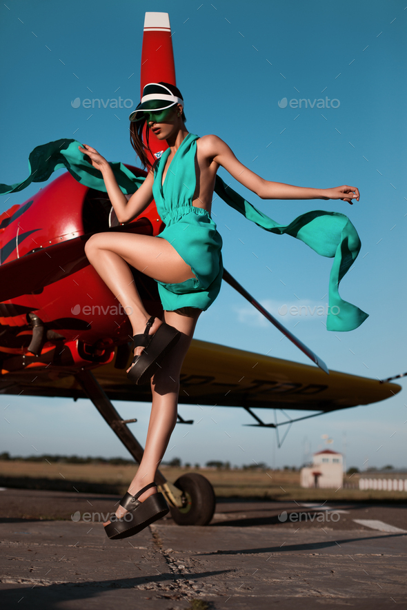 Fashion pilot girl in a visor posing next to propeller plane at runway during sunset - Stock Photo - Images