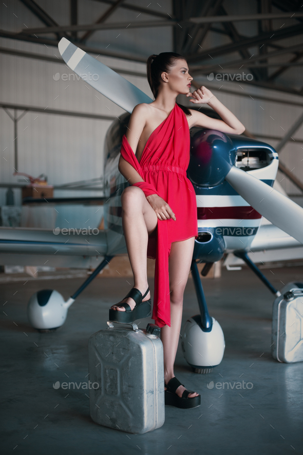 Fashion photo of model girl in red dress posing with jerrycan next to propeller plane in the garage - Stock Photo - Images